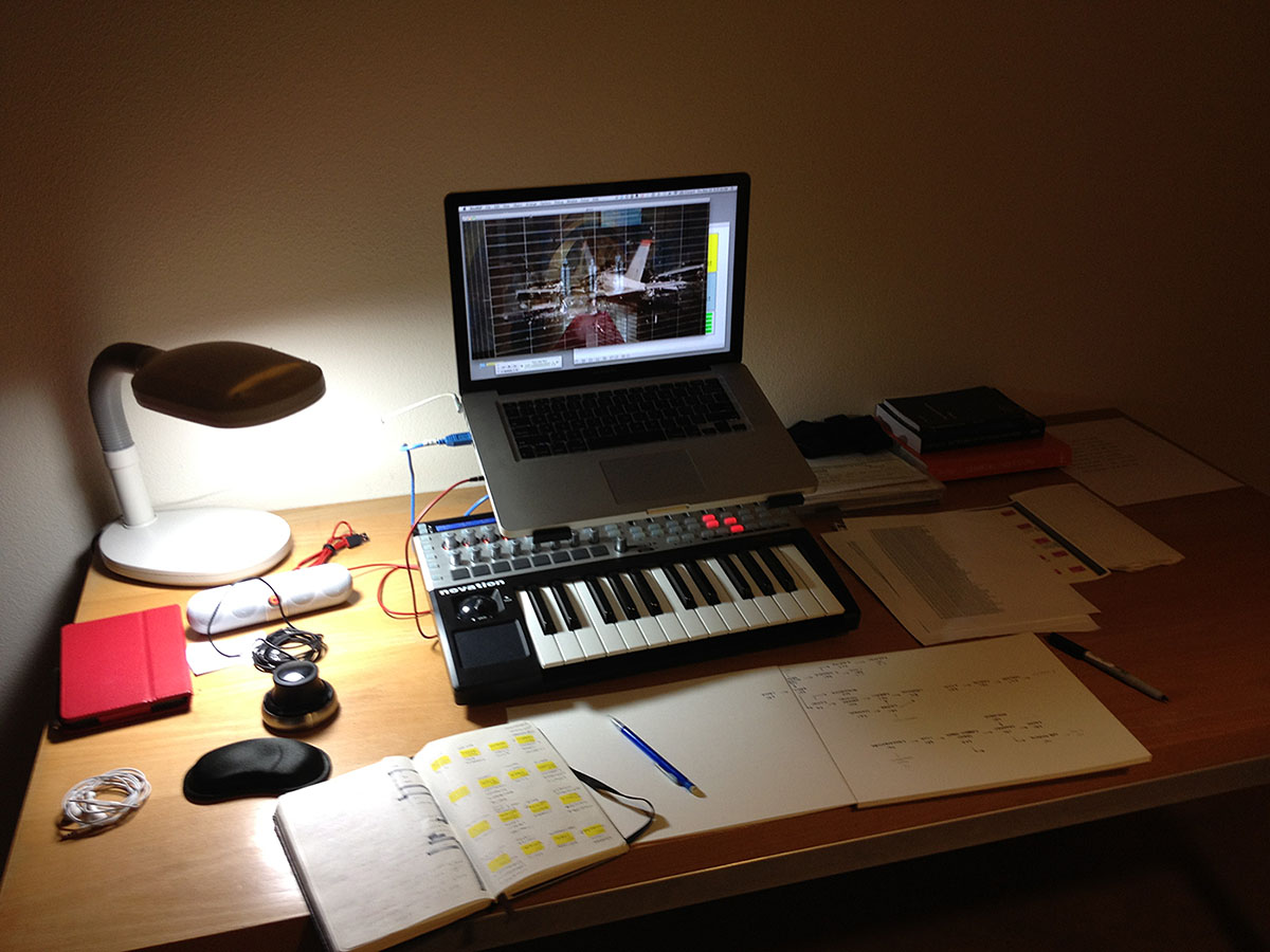 desk with laptop, midi controller, and image of a plane crashing into a building